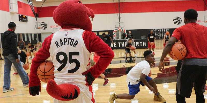 Toronto Raptors in a number 95 jersey watches kids execute basketball drills