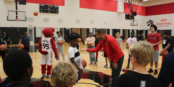 Raptors Assistant Coach Jama Mahlalela gives adivce to a kid as he attemps a drill. Ohters watch in a cirlce around them.