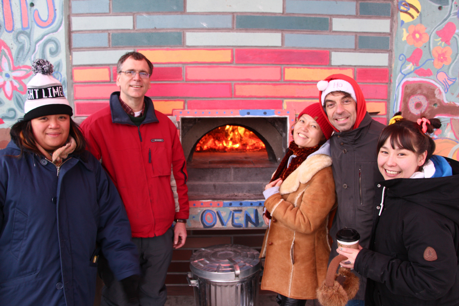 Winter Solstice volunteers pose next to a wood burning oven where they will bake treats.