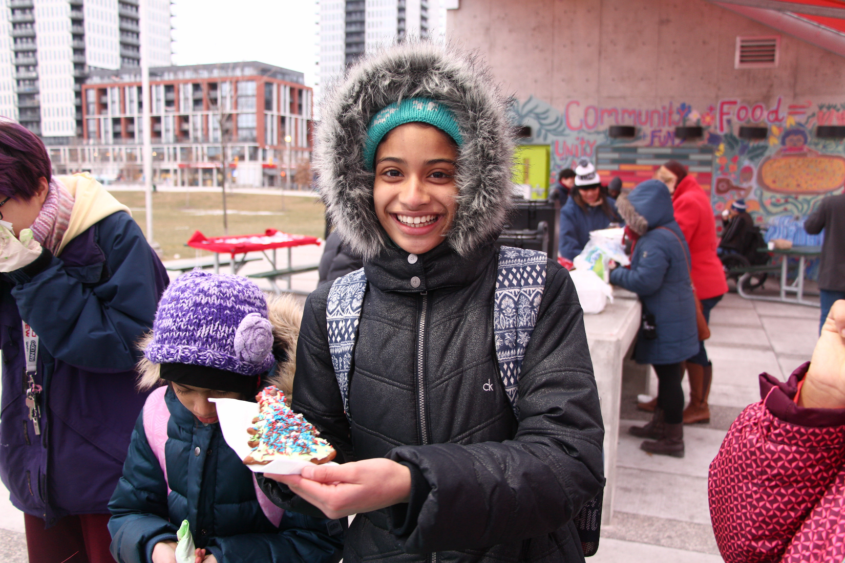A girl shows off her decorated gingerbread cookie. With festivities in the the background.