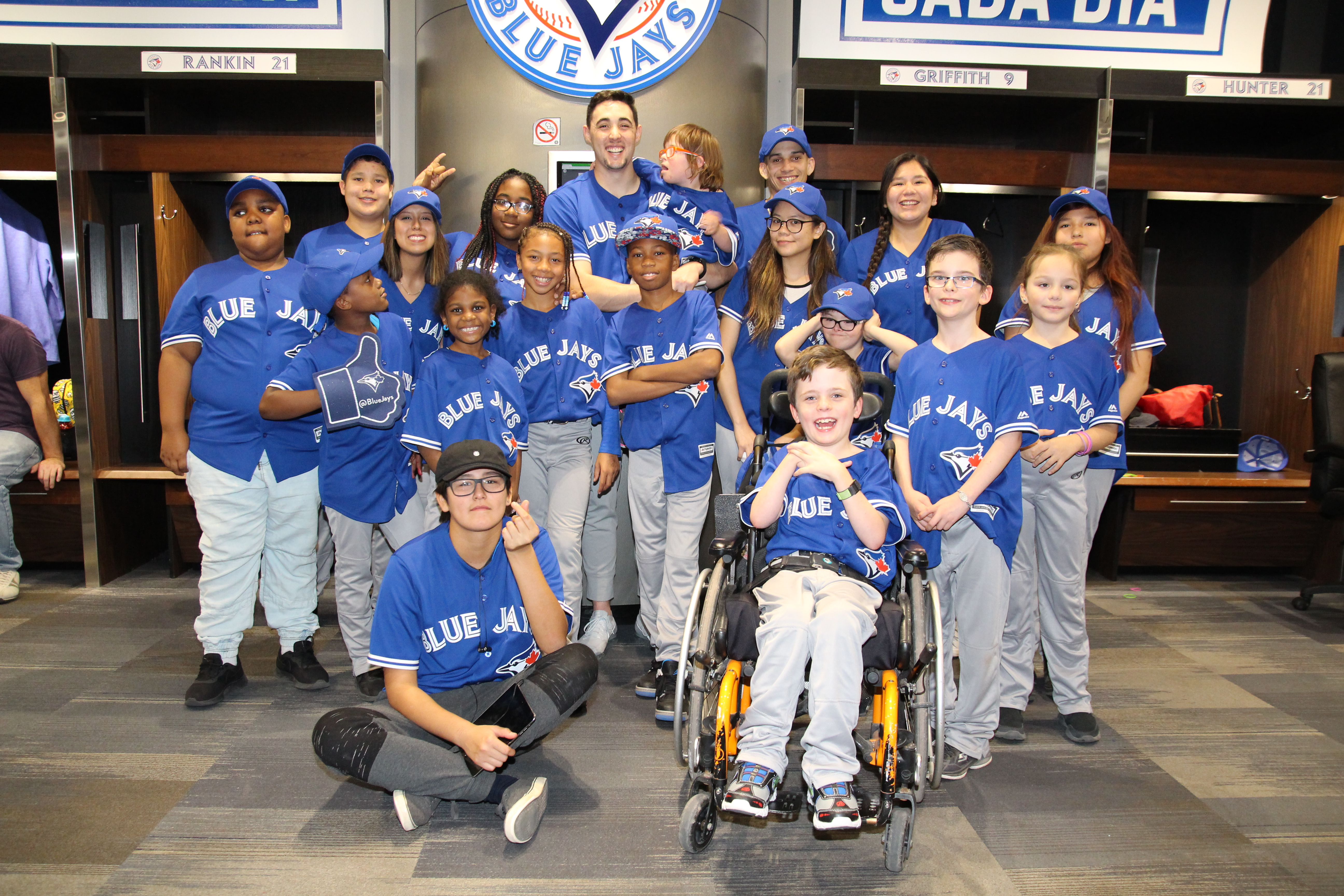 Unstoppable Kids pose in Blue Jays uniforms with Blue Jays pitcher Aaron Sanchez