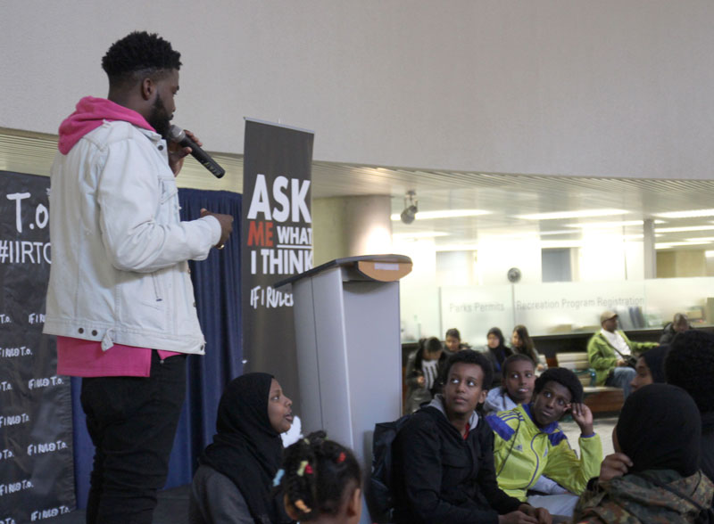 MC Femi Lawson (standing on the left), speaking to  a group of young people