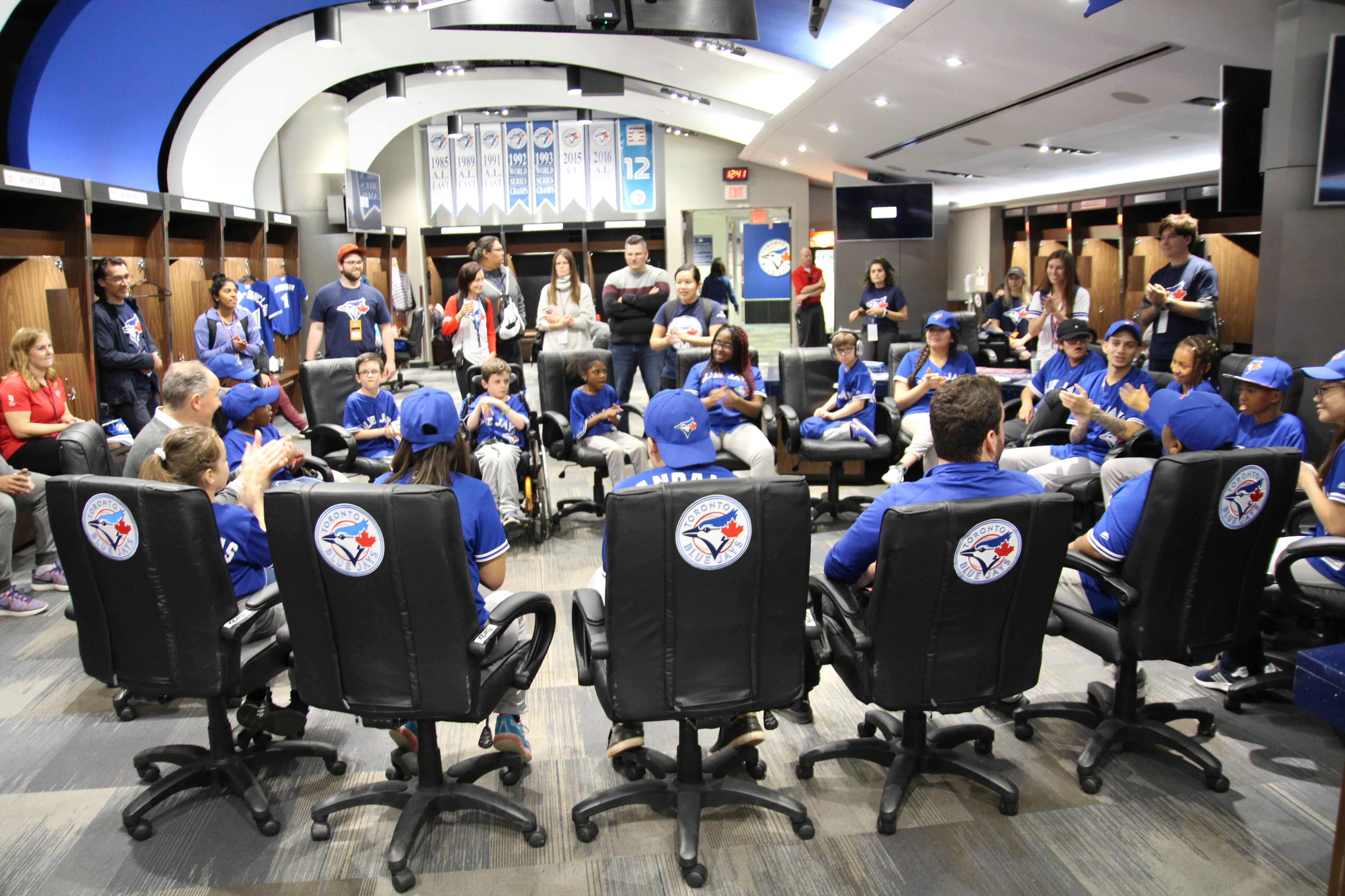 Unstoppable Kids sit in a circle in the BLue Jays dressing room playing a game.