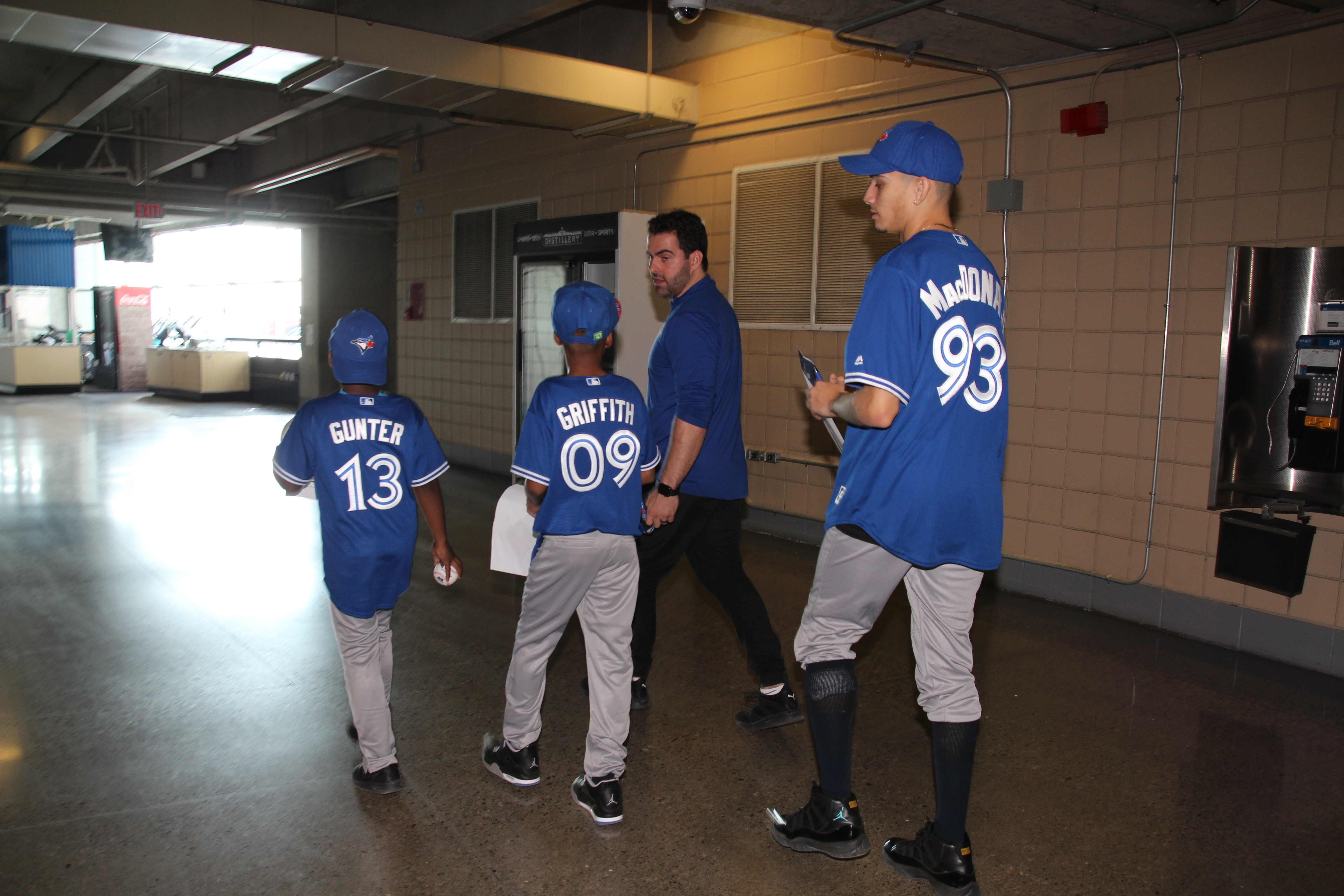 Jays Care staff member giving a group of Unstoppable Kids a tour of the Rogers Centre.