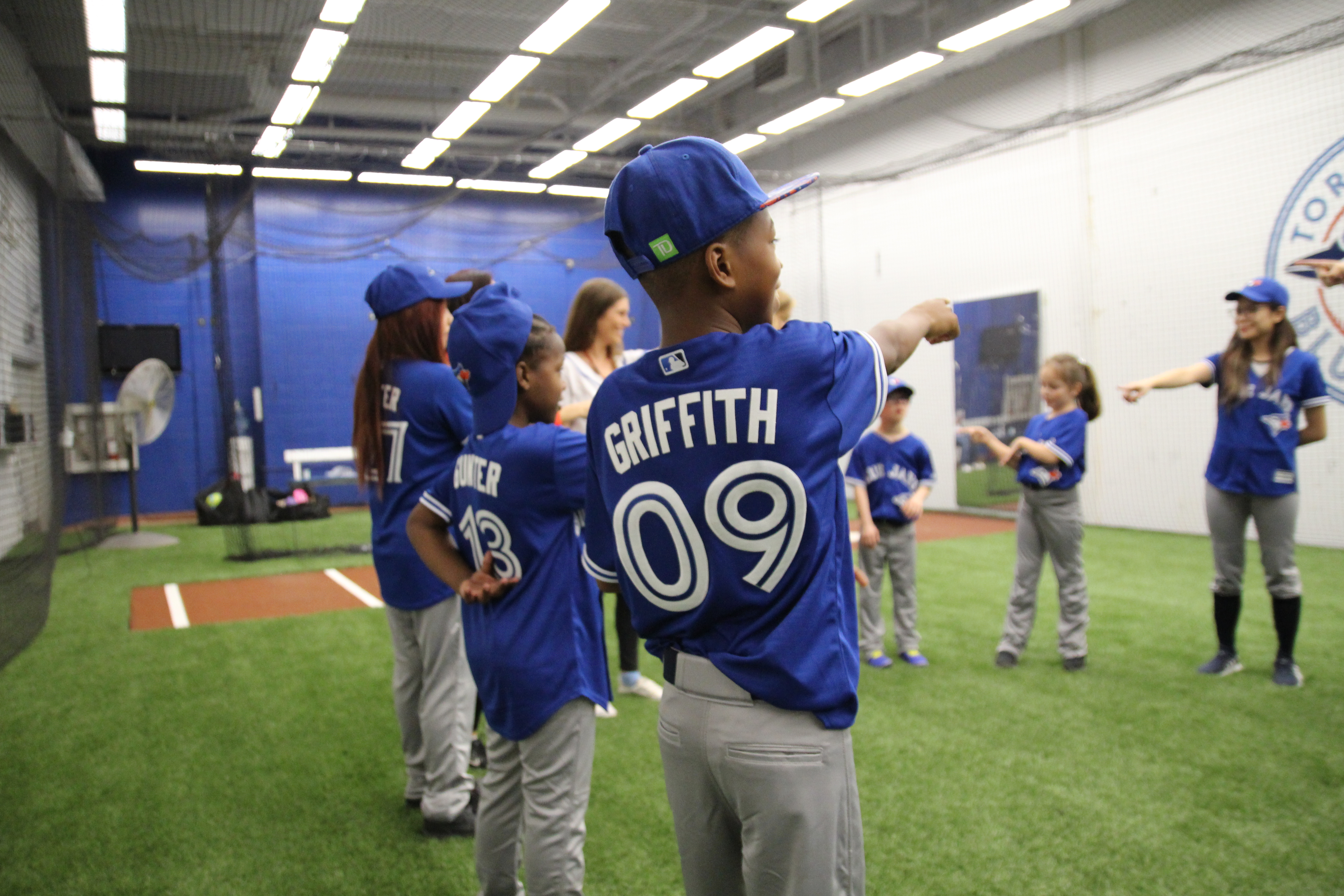 Group of kids stand in Blue Jays batting cage playing a game. Each stands in a circle pointing to their partner.