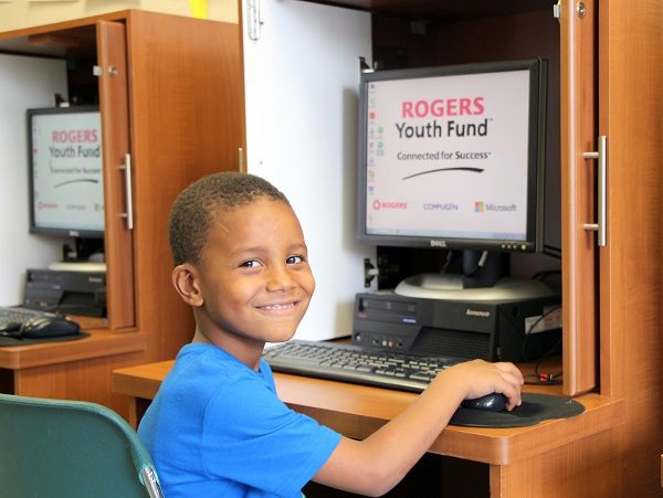 A young resident poses while using one of the computers available in the Cooper Mills community lab.