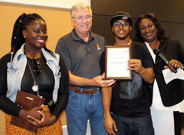 Toronto Community Housing Staff present an award to a YouthWorx participant