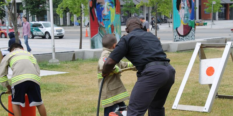 A Toronto Fire Services staff helping a young resident how to aim a fire hose at the junior fire fighter challenge.