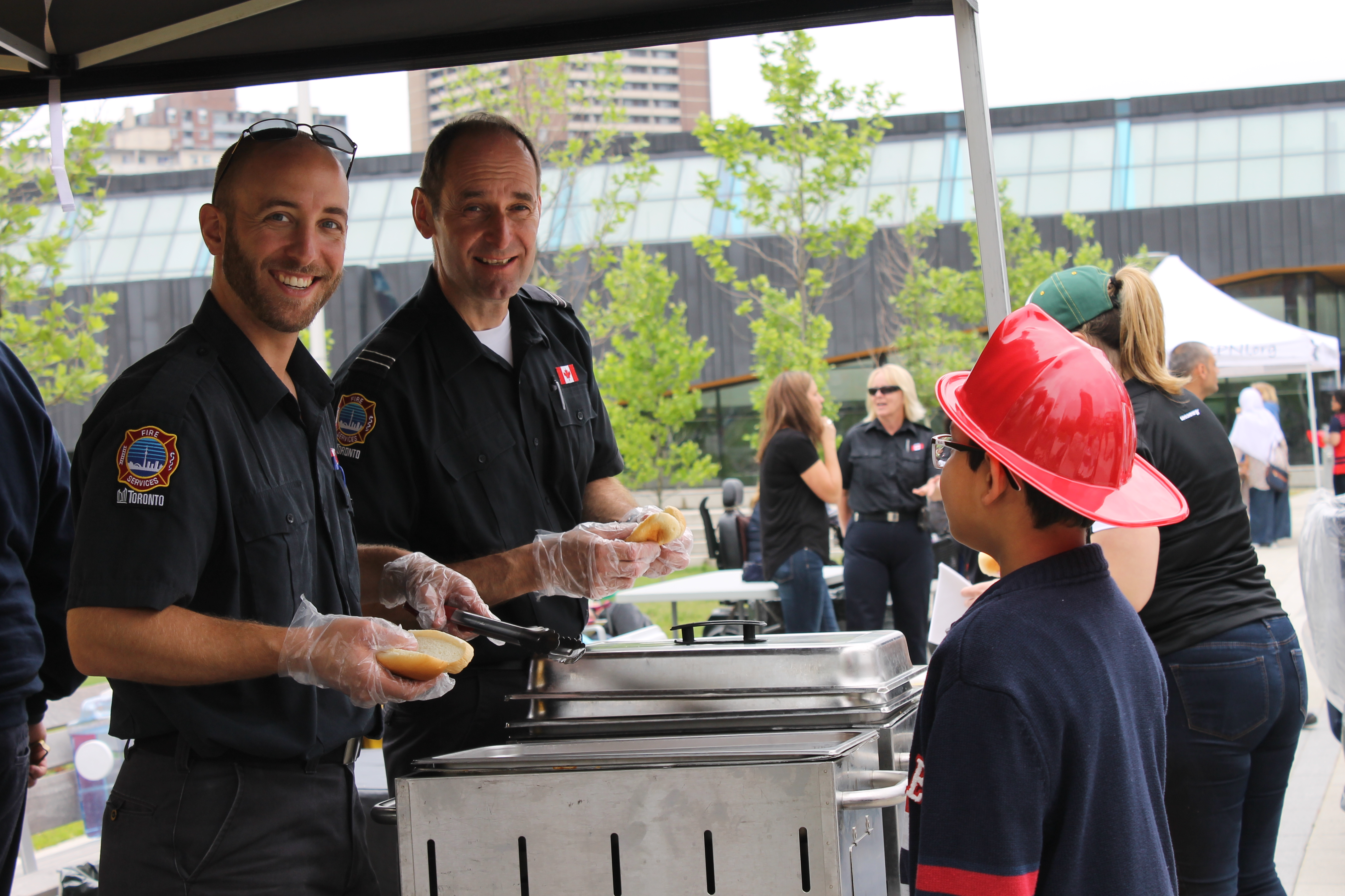 Toronto Fire Services staff are preparing hot dogs for residents at the Community BBQ.