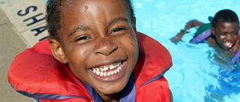 smiling boy wearing red life jacket and standing next to an outdoor swimming pool