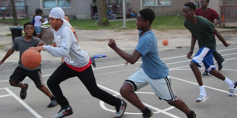 Neptune residents chase the ball on their new basketball court