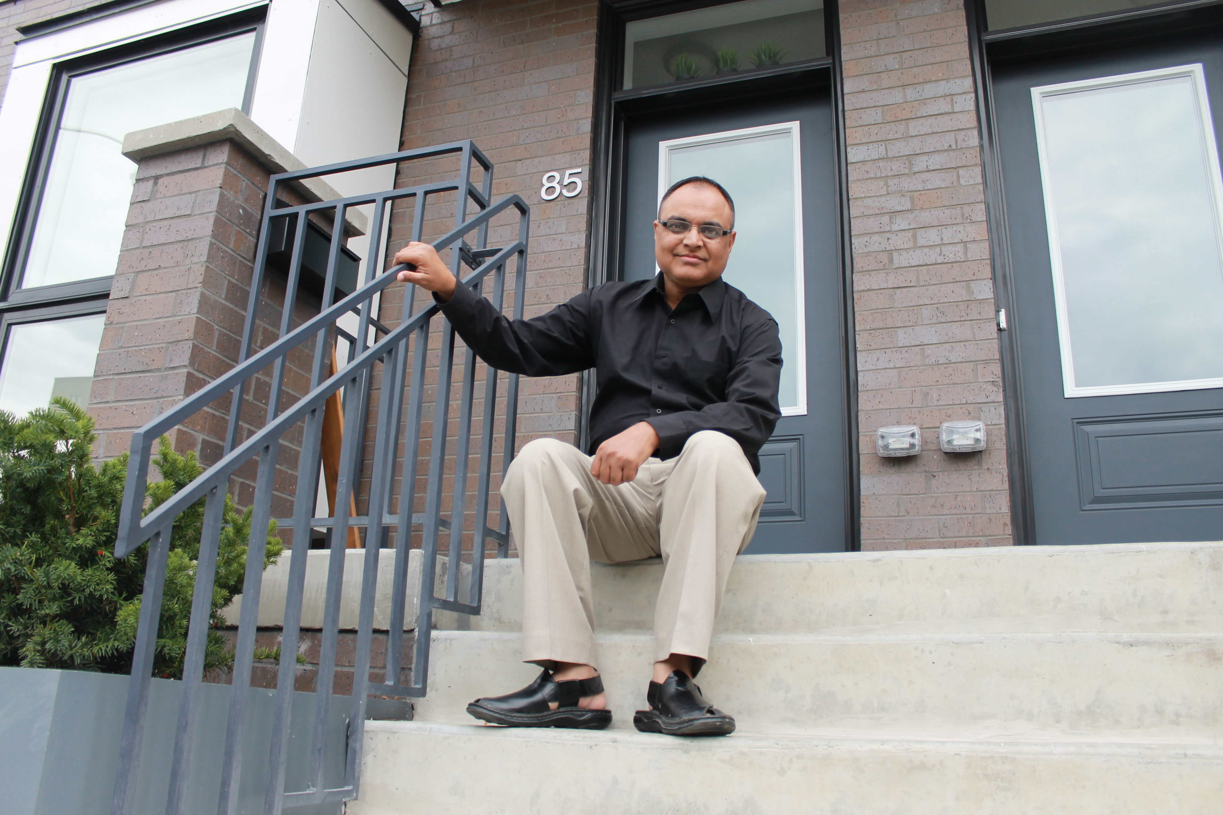 Waseem Tahir sits infront of his new townhome at Alexandra Park.