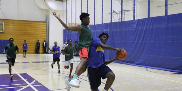 Two players players from  opposing teams play basket ball and come in contact by the basket.