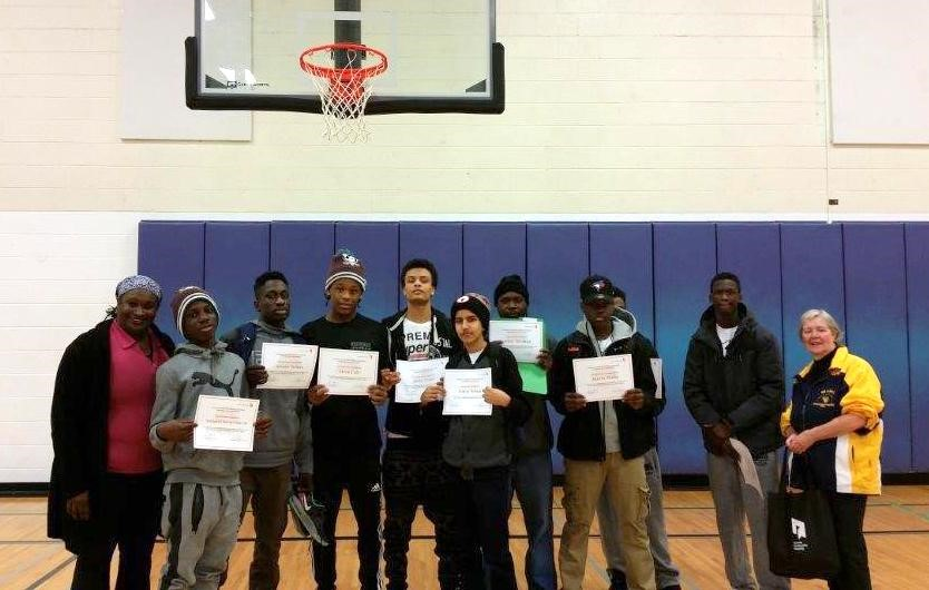 Midnight Madness Basketball participants share smiles with staff during a certificate presentation.