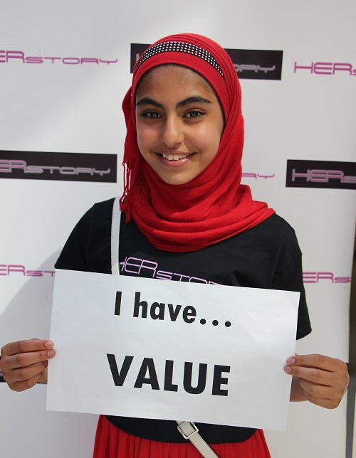 "Smiling young girl, wearing a hijab and holding a sign that reads ""I have value"""