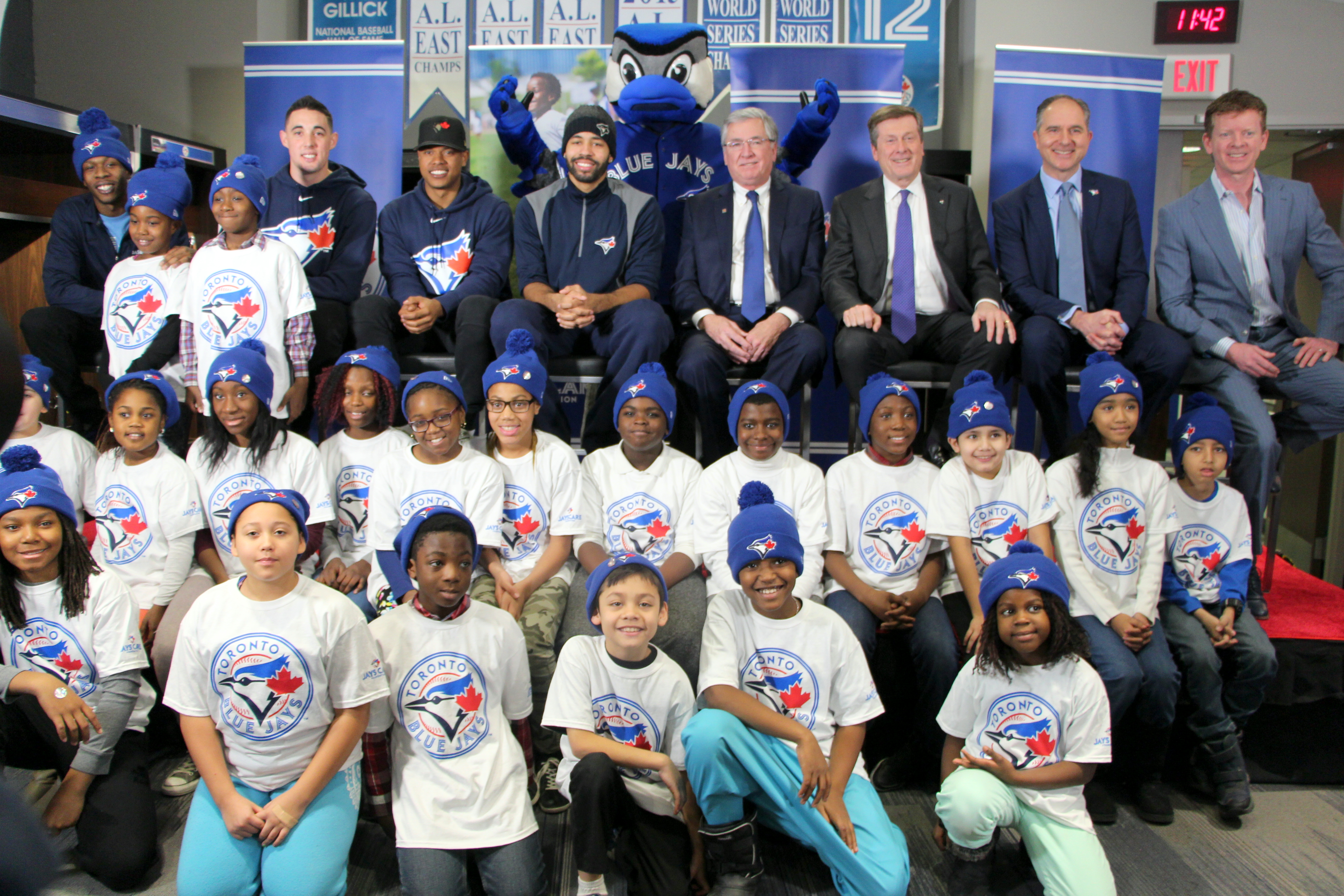 photo of diverse group of youth in Tronto Blue Jays hats and t-shirts, in front of Blue Jays players and the Mayor