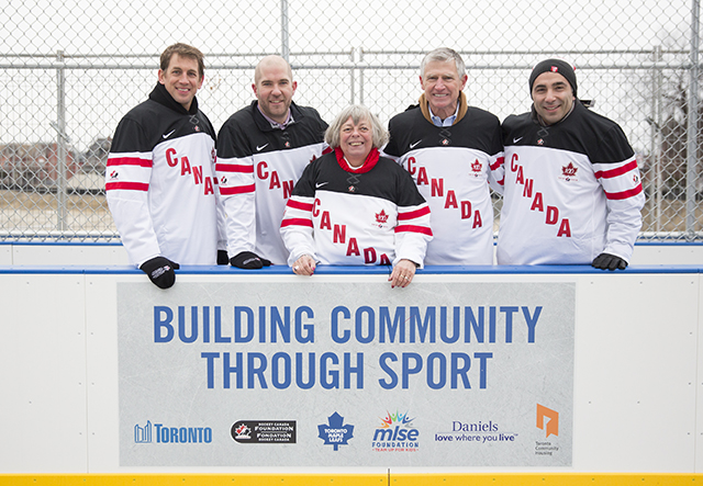 City Councillor, Pam McConnell and Bud Purves and others pose on the new rink in Hockey Canada jerseys.