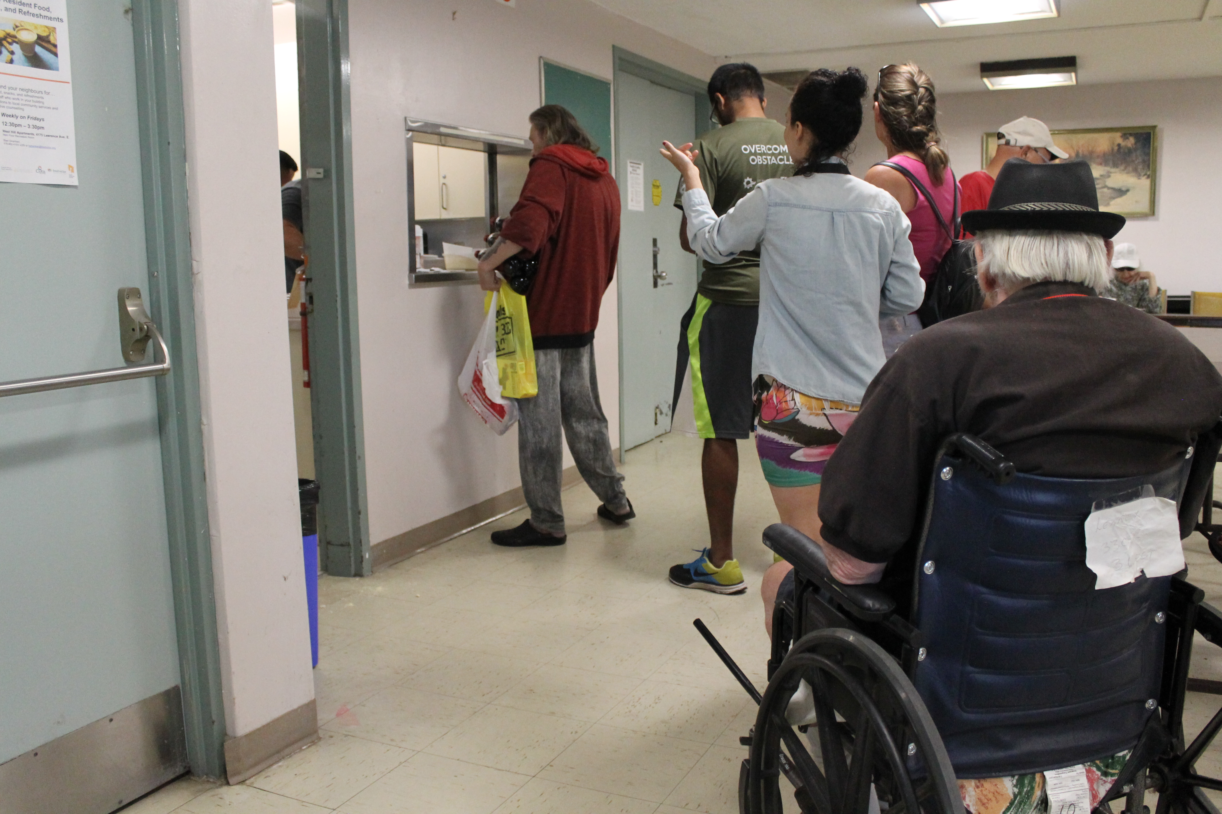 Residents line up in the building's recreation room for a tasty lunch.