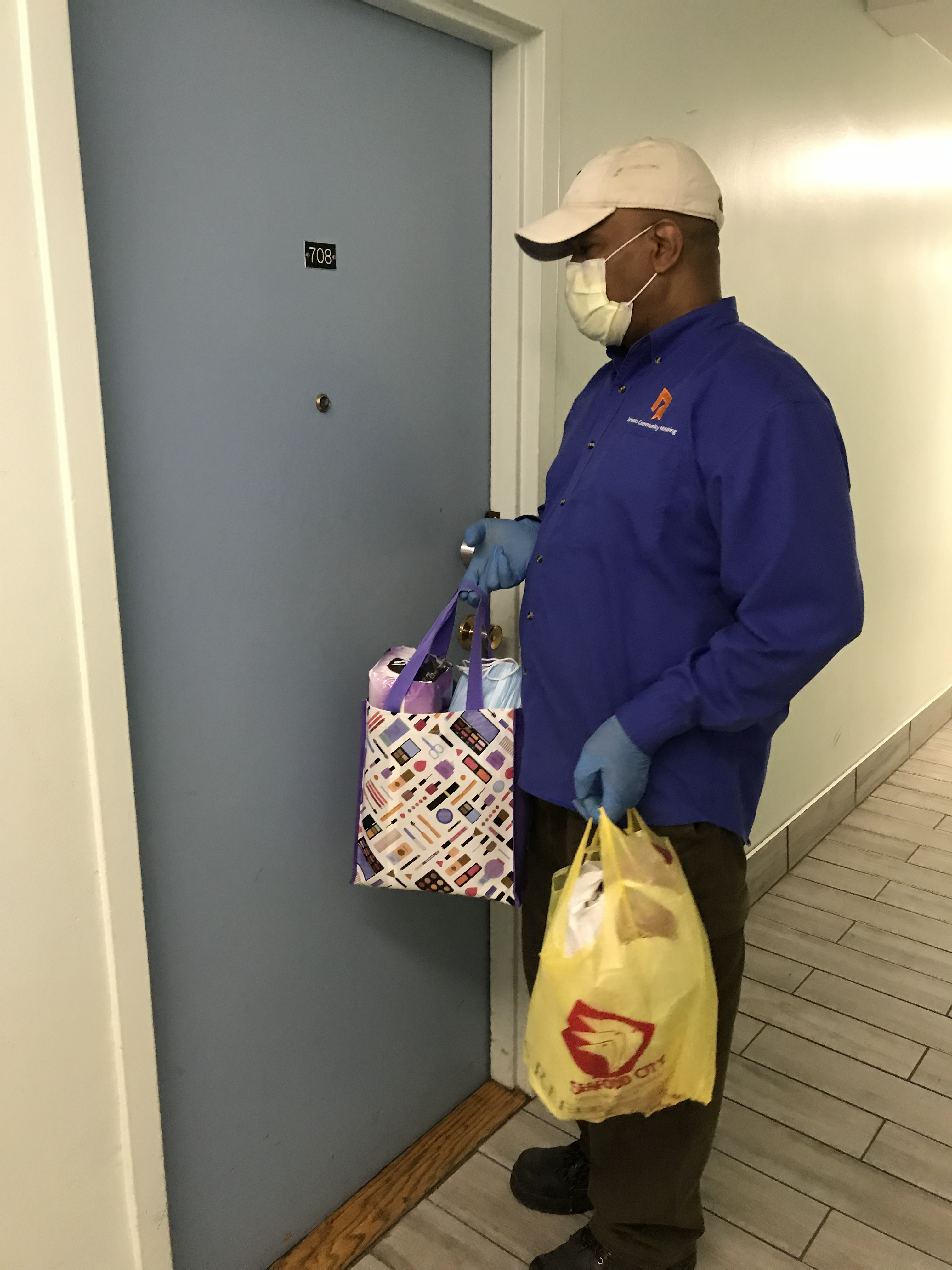 A TCHC male staff delivering bags of toiletries to a tenant.
