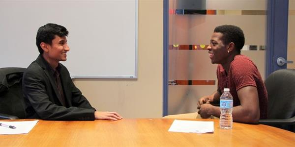 A young man named Devante (right) begins his job interview with a UPS human resources staff member.